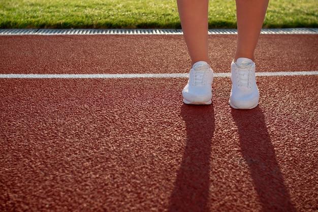 레드 코트에 다리에서 그림자입니다. 검은색 레깅스와 운동화를 신고 지역 경기장에서 아침 시간을 보내는 여성 주자를 닫습니다. 여성 스포티 모델. 스포츠 활동의 개념입니다.