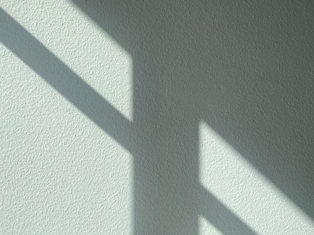 灰色の粗い壁に太陽からの影。抽象的なテクスチャ