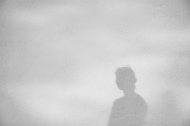 Shadow of a girl on a white concrete wall