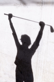 Shadow of a golfer on the wall under the lights