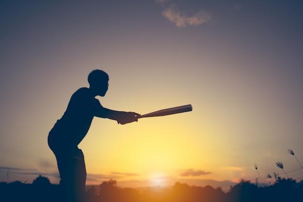 Shadow of kids playing baseball on sunset background
