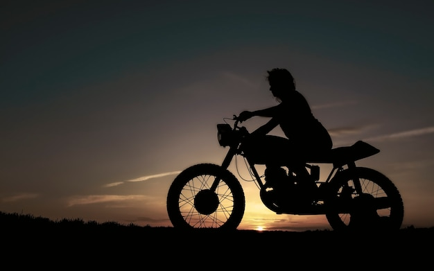 日没のバイカーの女の子の影、自転車の女の子のシルエット。