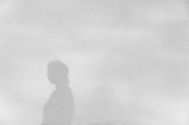 Тень девушки на белой бетонной стене