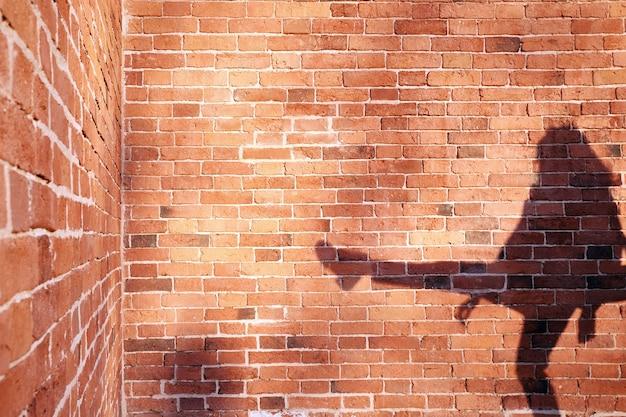 벽돌 벽 배경에 남자의 그림자입니다.