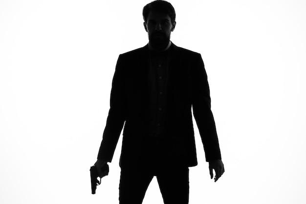 Тень человека с пистолетом в руках, прицеливающего свет детективного преступления.