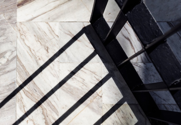 Тень кованой двери на белом мраморном полу