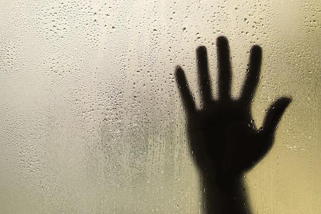 Тень руки за матовым стеклом с каплями воды