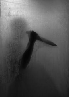 욕실에서 젖빛 유리 뒤에 날카로운 칼을 들고 공포 살인자의 그림자