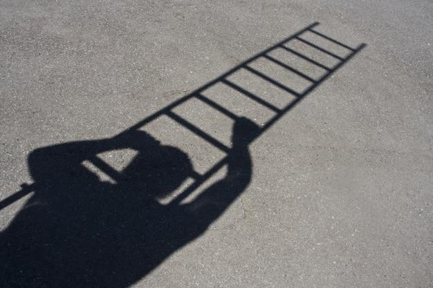 アスファルトの上をはしごを登る男の影