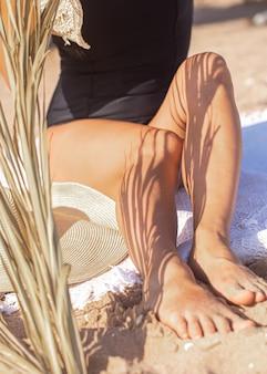 Тень пальмовых ветвей на теле женщины, расслабляющейся на пляже. отдых и летняя концепция.