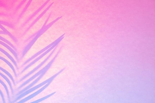 Тень пальмового листа в модной двухцветной подсветке. абстрактный фон в розовых сиреневых неоновых тонах.