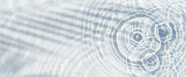 Тень пальмового листа на прозрачной воде и падающих каплях воды. вид сверху, плоская планировка. баннер.