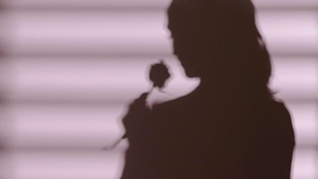 バラを持った女性の影