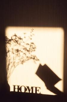 碑文の家、乾燥した花束、女性の手に開いた本と壁に影。