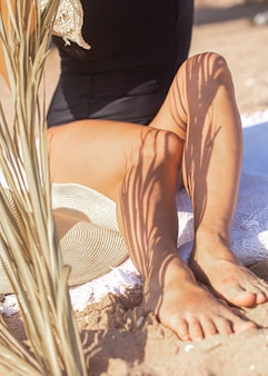 Shadow of palm branches on the body of a woman relaxing on the beach. rest and summer concept.