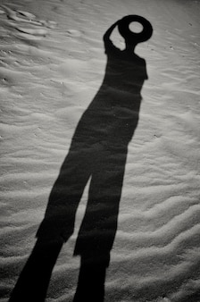 A shadow in the sand of a man with a circle instead of a head