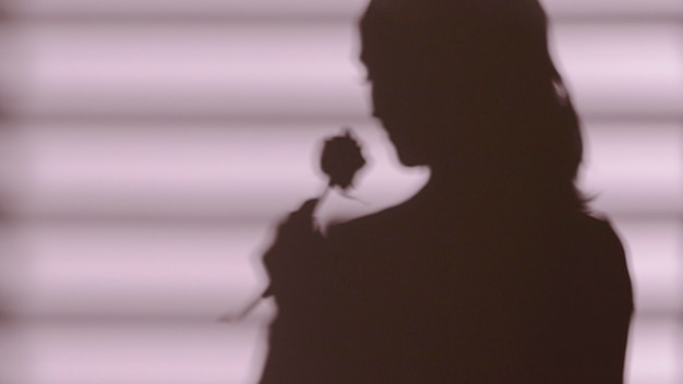 Shadow of woman holding a rose