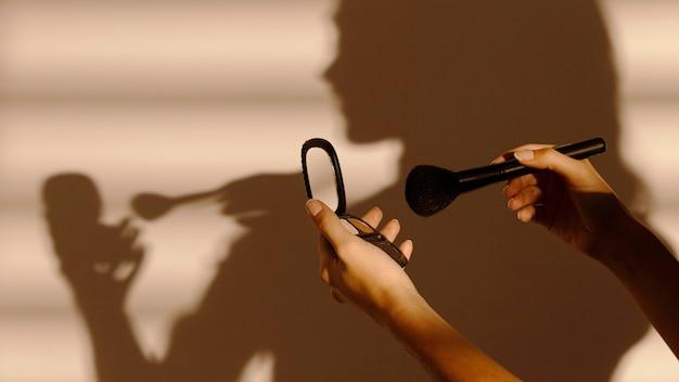 Ombra di donna che utilizza diversi cosmetici