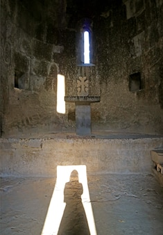 Shadow of a woman wearing headdress reflecting on the floor of an old stone church