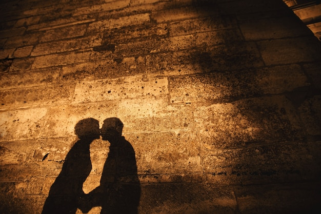 The shadow of a young kissing couple on the wall of the old castle