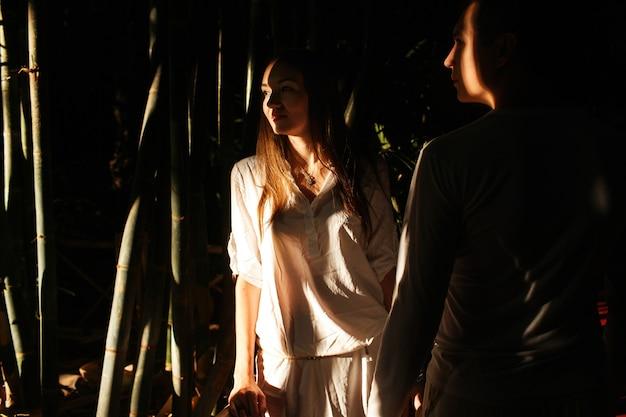 Shadows hide beautiful couple walking in an african botanic garden