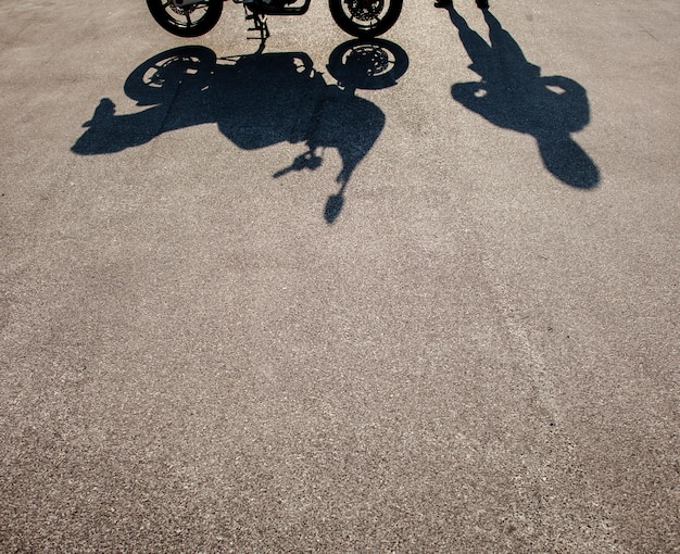 Shadows of man and motorbike