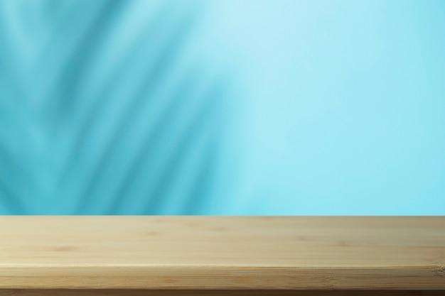 手のひらの影と空の木製テーブル