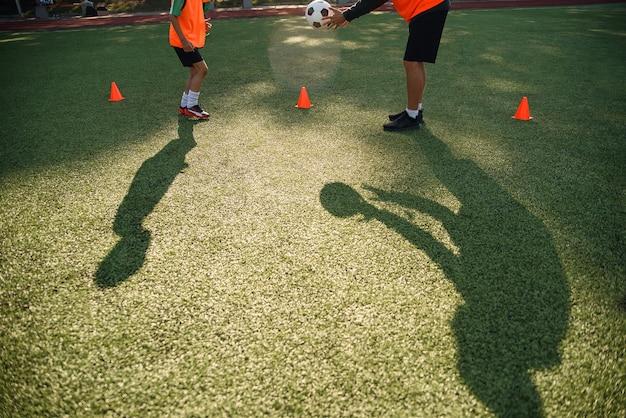 サッカーのコーチの影が若いサッカー選手とボールキックを訓練します。