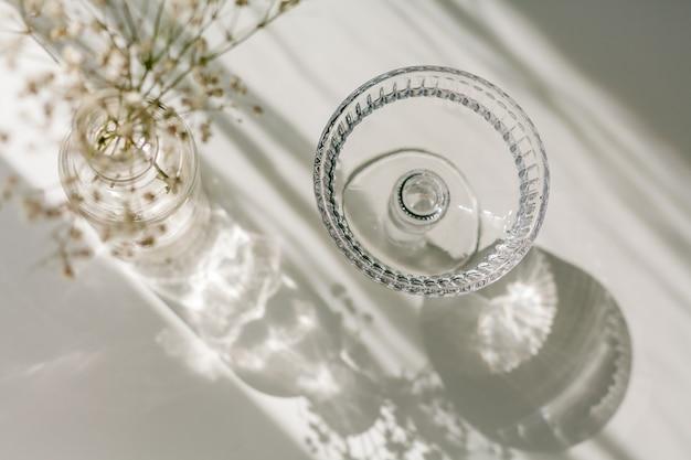 유리와 꽃에서 흰색 배경에 그림자. 빛의 광선에 유리 꽃병에 말린 꽃. 집.