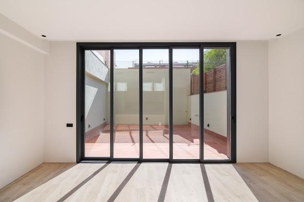 大きな窓からの日光からの床の影改装された木の床の新しい部屋...