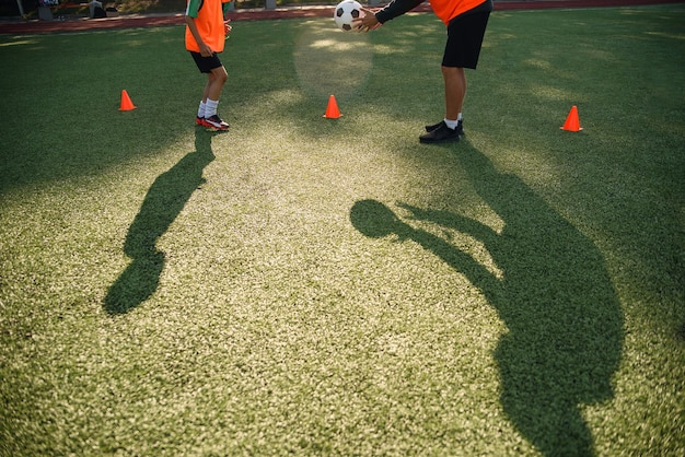 Shadows of soccer coach trains ball kicks with young football players.