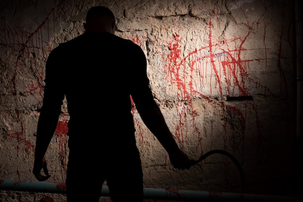 Shadowy figure holding blade near blood stained wall for concept about murder and scary halloween holiday