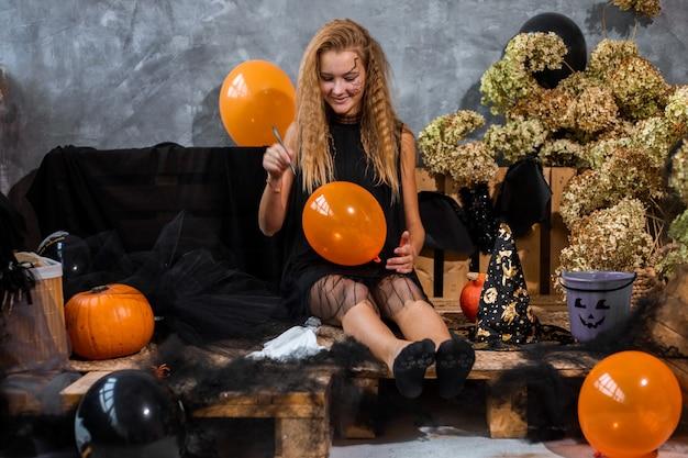 그녀의 손에 유령과 함께 할로윈 휴가를위한 검은 색과 오렌지색 톤의 장식 중 얽히고 설킨 10 대 소녀
