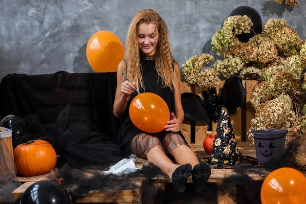 주황색 풍선을 들고 할로윈 휴가를 위해 검은색과 주황색으로 장식된 10대 소녀