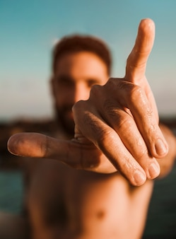 Человек показывая знак руки shaka