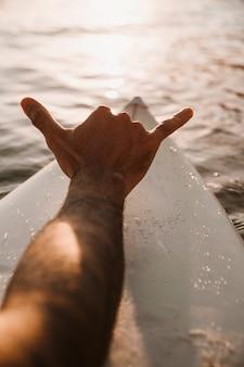 Человек показывая знак руки shaka на доске для серфинга