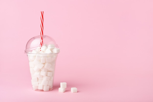 ピンクの背景に砂糖でいっぱいのストローでガラスを振る。不健康な食事療法の概念。コピースペース、側面図。