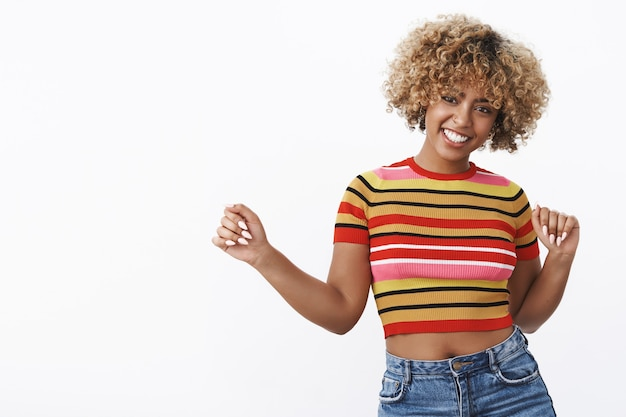 Shake it baby. portrait of good-looking stylish and happy young dark-skinned female with fair curly haircut and piercing in cropped top raising hands in dance smiling delighted and upbeat having fun