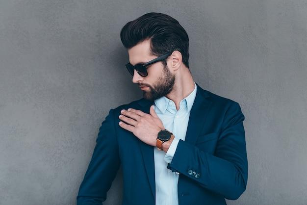 それを振り払います。灰色の背景に立っている間彼の肩から目に見えないほこりを振り払うサングラスの若いハンサムな男のクローズアップ