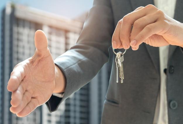 Домашние продажи shakehand и другая рука держит ключ дома. фон - это соглашение.