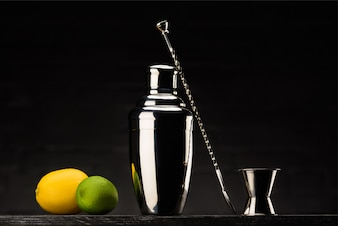 Shaker for preparing alcohol drink with lemon and lime on table isolated on black