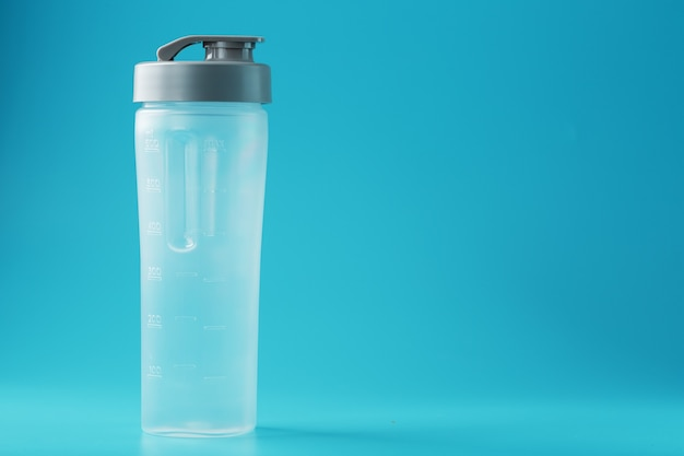 Shaker is an empty plastic smoothie cup on a blue surface