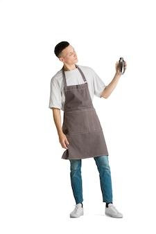 셰이커. 젊은 남성 백인 바리스타나 갈색 앞치마를 입은 바텐더가 웃고 있는 초상화. 하얀