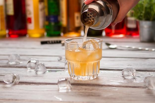 シェーカーはガラスに液体を注ぎます。角氷とオレンジ色の飲み物。飲料用のフレッシュグレープフルーツジュース。木製のテーブルで氷を溶かします。