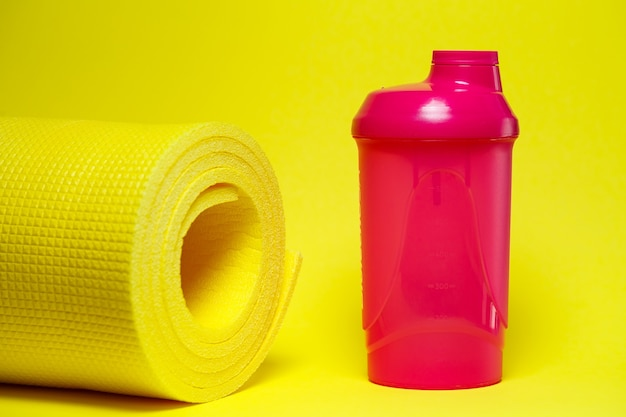 Шейкер спорт здоровый образ жизни спортивный коврик розовая бутылка с водой желтый фон яркие краски