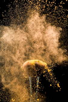 黄色の粉で揺れ化粧品のブラシ
