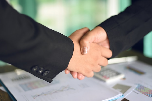 Shaking hand concept two successful asian business women shake hands
