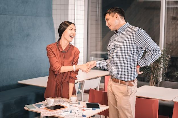 Трясущаяся рука. темноволосый мужчина в квадратной рубашке пожимает руку своему деловому партнеру, встречающему ее