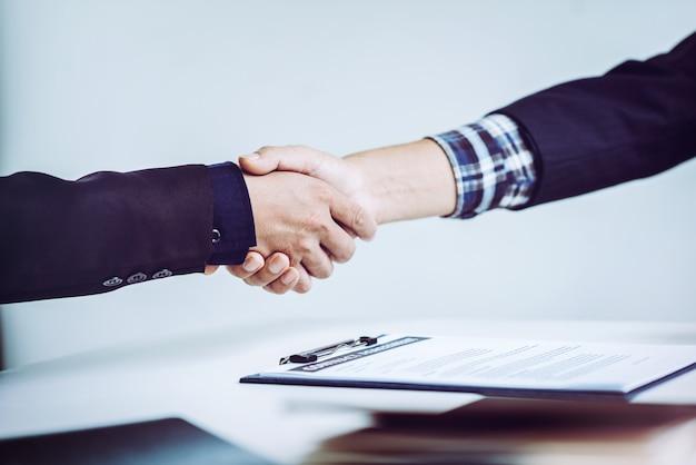 握手は、オフィス、ビジネスコミュニケーション、マーケティングの概念のビジネス人々を手します。