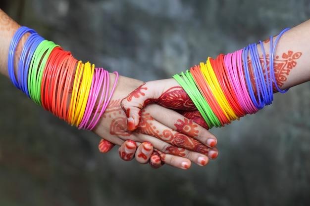 インド亜大陸でカラフルなブレスレットとヘナのタトゥーで飾られた握手